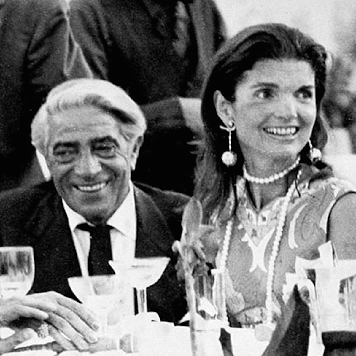 Greek shipping tycoon Aristotle & Jackie Onassis (his butler Alex Magnos R rear) sitting at table, celebrating 1st anniv. of their marriage w. friends at Neraida nightclub.  (Photo by Time Life Pictures/Pix Inc./The LIFE Picture Collection/Getty Images)
